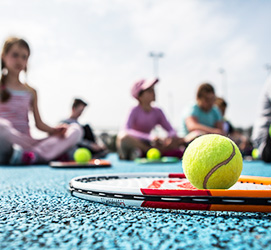 Tennis racket and ball close up, children in the backgrond